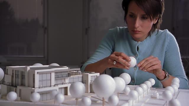 Medium shot female architect constructing model of building