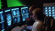 Medium shot female doctor and male patient looking at CT scan images on monitor