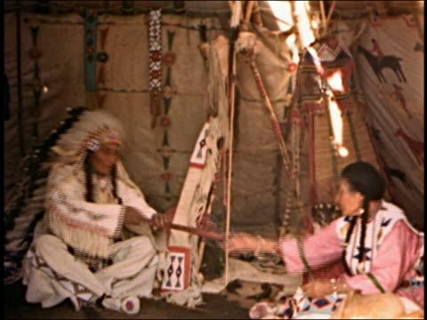 Medium shot  female Native American offers man pipe / male Native American smoking pipe / AUDIO