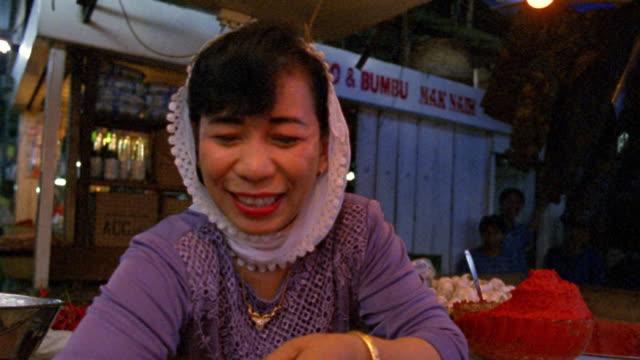 Medium shot female vendor putting peppers in bag in spice market / Bukittinggi, West Sumatra