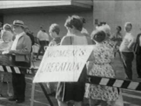 1968 medium shot feminist wearing 'Women's Liberation' sign at Miss America protest / Atlantic City NJ