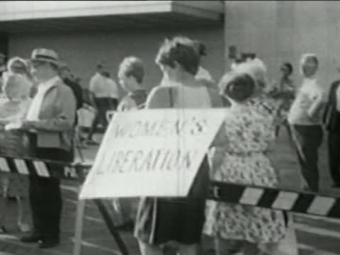 1968 medium shot feminist wearing 'Women's Liberation' sign at Miss America protest / Atlantic City NJ