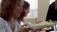Medium shot five women passing food at brunch table/ San Francisco, California
