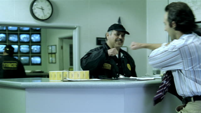 Medium shot foreman greeting security guard at desk and signing-in on clipboard / pan rushing into warehouse