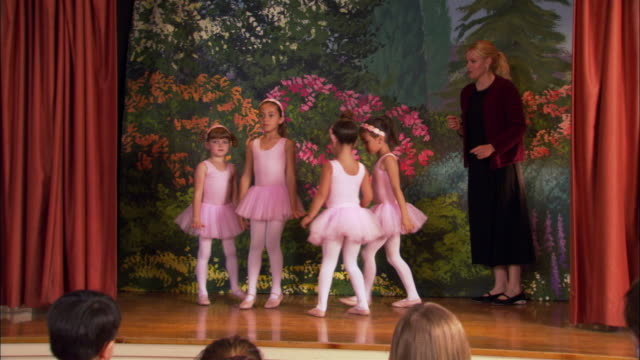 Medium shot four girls wearing tutus holding hands and dancing in a circle / teacher at side of stage / girls posing and curtsying