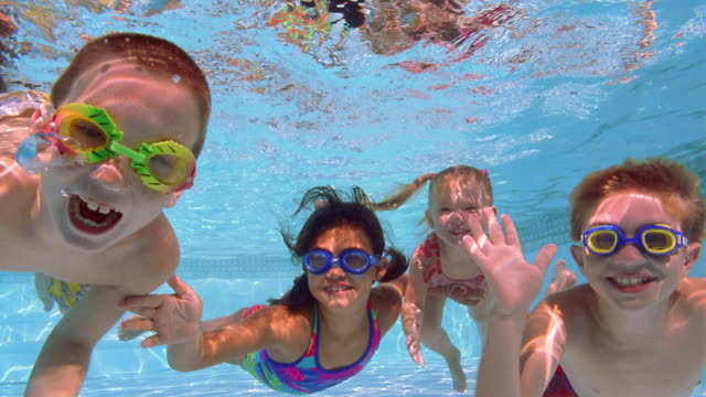 Medium shot four kids swimming underwater, smiling, and waving at camera