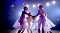 Medium shot four young ballerinas in tutus holding hands and circling on stage / twirling in place