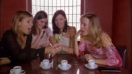 Medium shot four young women sitting at table and looking at woman's diamond ring