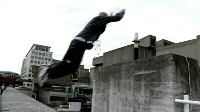 Medium shot freerunner jumping from roof and grabbing ledge of another building