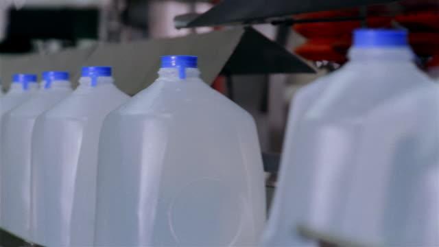 Medium shot gallon plastic water jugs on a conveyor belt at a water purification plant / San Antonio, Texas