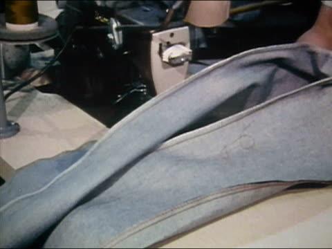 1980 medium shot garment worker sewing denim jeans at jeans factory / AUDIO