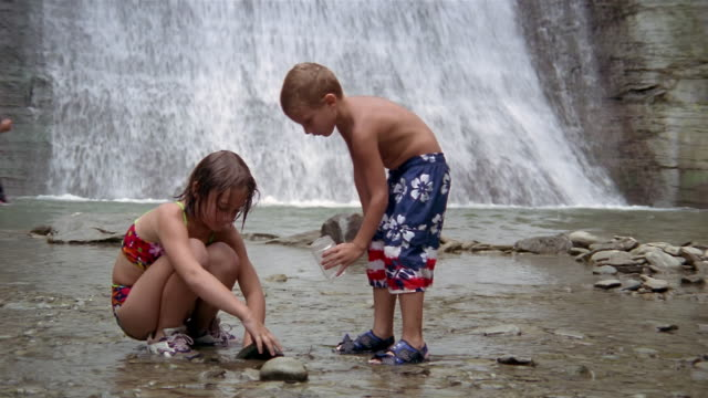 Medium shot girl and boy collecting specimens in stream at foot of waterfalls/ Stony Brook State Park, New York