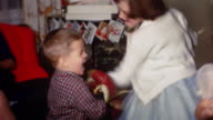 1958 medium shot girl and younger boy boxing in living room / greeting cards hanging in background