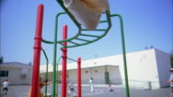 Medium shot girl hanging upside down on playground monkey bars and waving at CAM