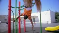 Medium shot girl hanging upside down on playground monkey bars / boy hanging upside down in background