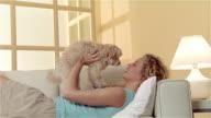 Medium shot girl lying on sofa, holding Maltese-Toy Poodle mix on chest and kissing dog