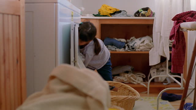 Medium shot girl removing clothes from dryer, piling them in basket and lifting basket