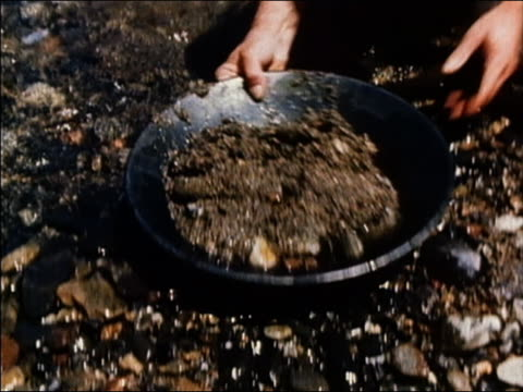 1965 medium shot gold prospectors sifting and washing sieves in stream / 'The Gold Rush' / AUDIO