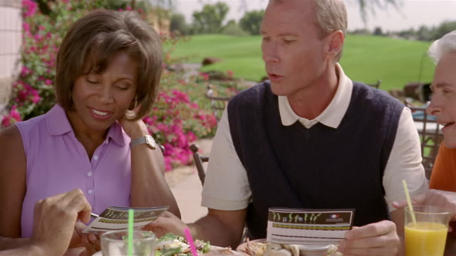 Medium shot golfing friends having lunch at clubhouse and comparing score cards/ Phoenix, Arizona
