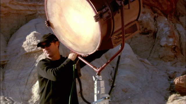 Medium shot grip rotating large light on film set / Red Rock Canyon State Park, California