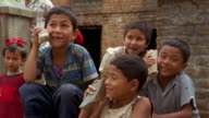 Medium shot group of children pretending rocks are cell phones / Nepal