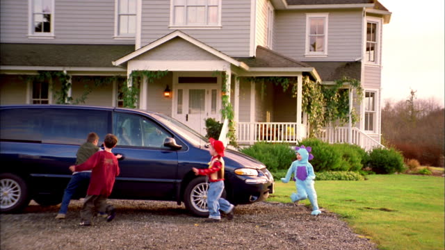 Medium shot group of children running to van parked in driveway and climbing inside / woman closing van door