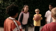 Medium shot group of kids facing two boys choosing teams / boy left alone bouncing ball and looking sad