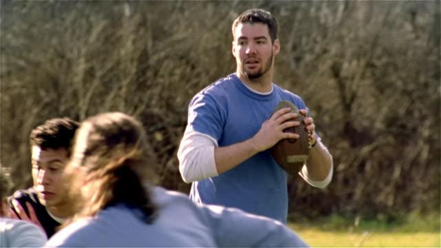 Medium shot group of men and women playing football/ Maine