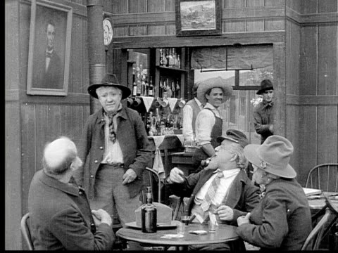 1913 B/W Medium shot Group of old men shaking hands, smoking pipes and talking around table in bar / USA