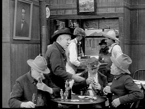 1913 B/W Medium shot Group of old men talking and smoking pipes around table in bar while another man leaves / USA