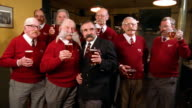 Medium shot group of senior men with identical red sweaters toasting their pints of beer
