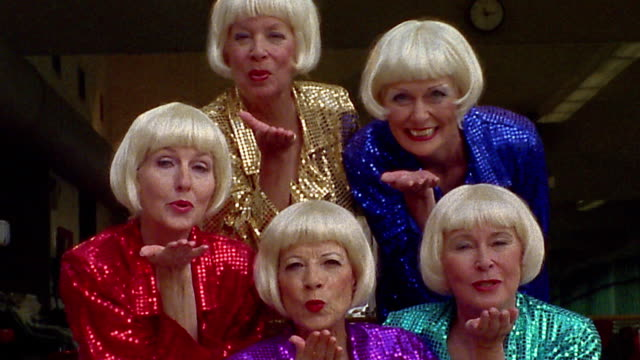 Medium shot group of senior women wearing identical blonde wigs and matching sequinned dresses blowing kisses