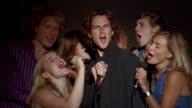 Medium shot group of young men and women singing karaoke + laughing / man in center