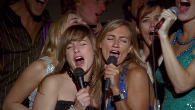 Medium shot group of young men and women singing karaoke + laughing