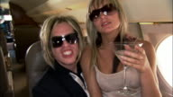 Medium shot Groupie drinking martini and sitting on rock star's lap on private airplane