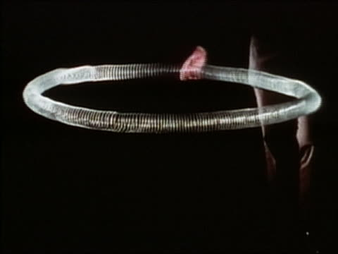 1971 medium shot hand causing vibrations in a large, circular Slinky-like spring