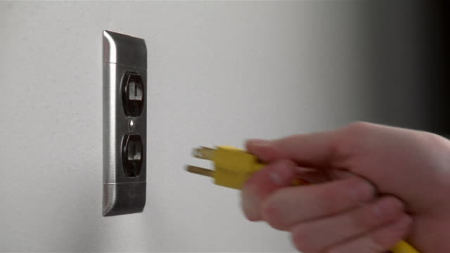 Medium shot hand inserting yellow plug into wall outlet and pulling it out again