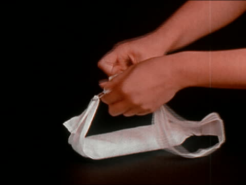 1970 medium shot hands attaching feminine napkin to belt, stretching elastic and holding it up to demonstrate / AUDIO