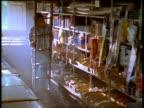 Medium shot hardware store clerk climbing ladder / removing spray can from shelf