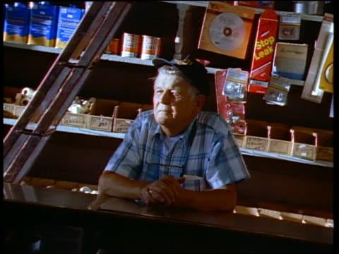 Medium shot hardware store clerk leaning on counter