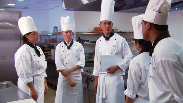 Medium shot head chef (or culinary instructor) talking to chefs (or culinary students) in kitchen / Auckland