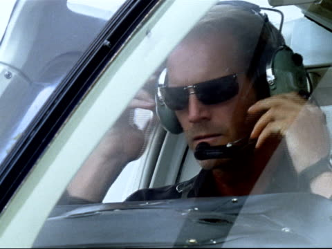 Medium shot helicopter pilot putting on headphones and checking equipment