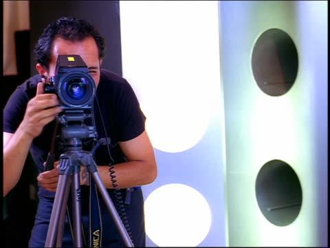 Medium shot Hispanic photographer gesturing and shooting photographs in studio with flashes