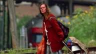 Medium shot homeless woman walking across train tracks with shopping cart