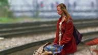 Medium shot homeless woman with shopping cart next to train tracks