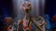 Medium shot hostile alien approaching and talking or hissing at CAM/ holding long fingernails up to CAM