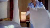 Medium shot housekeeper making bed in hotel room / placing tray of chocolates on bed