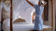 Medium shot housekeeper making bed in hotel room
