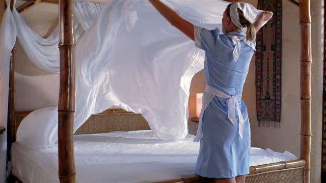 Medium shot housekeeper making bed in hotel room