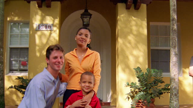 Medium shot interracial couple and young boy smiling in front of house